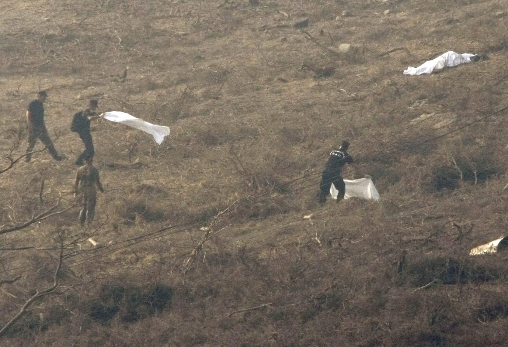 Άνδρες της ΕΜΑΚ σκεπάζουν πτώματα που έχουν εκσφενδονιστεί στο απέναντι βουνό.