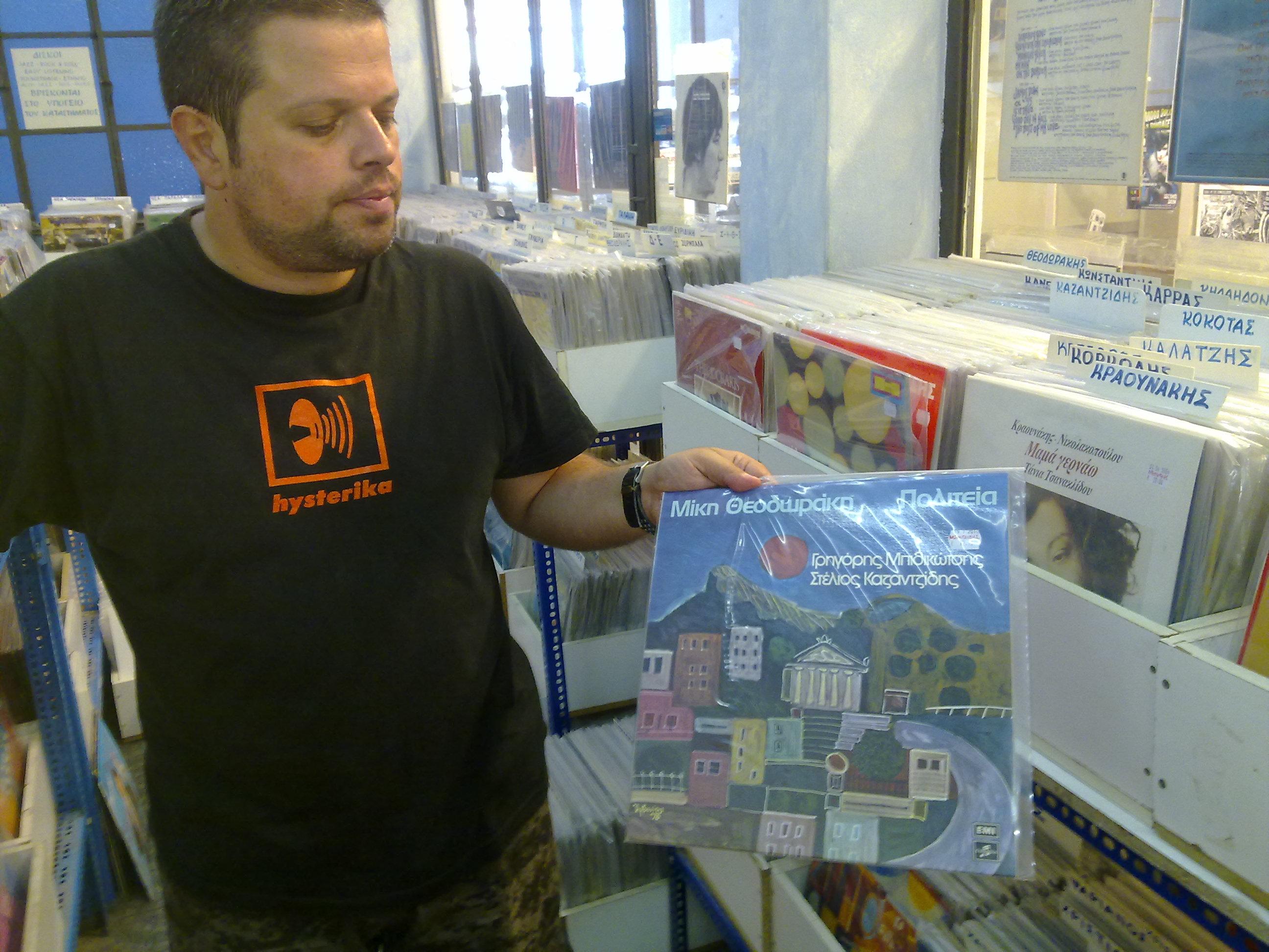 Ο Μανώλης, δείχνει στον φακό του Newsit μεταχειρισμένο δίσκο του Θεοδωράκη που κοστίζει 12,20 ευρώ.