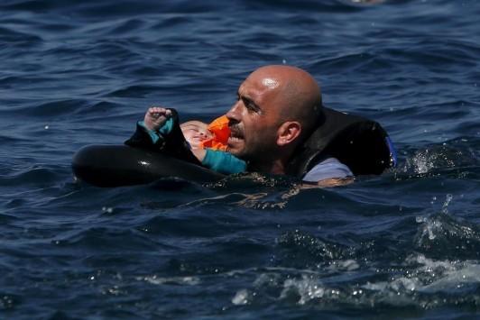 Η φωτογραφία της ημέρας: Πρόσφυγας με μωρό στην αγκαλιά κολυμπάει προς τη Λέσβο