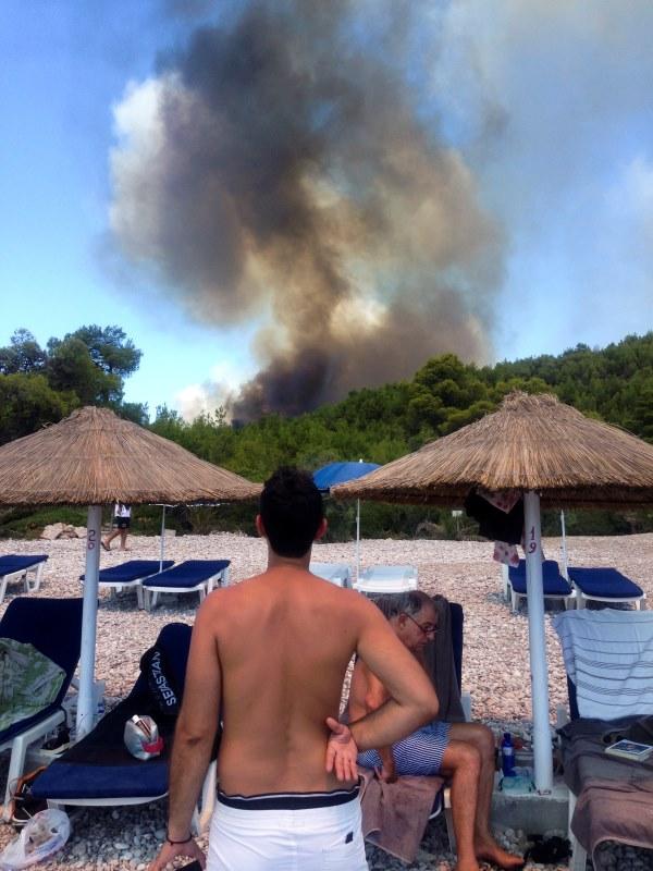 Άνθρωποι βλέπουν τη μεγάλη φωτιά από παραλία του νησιού - ΦΩΤΟ REUTERS
