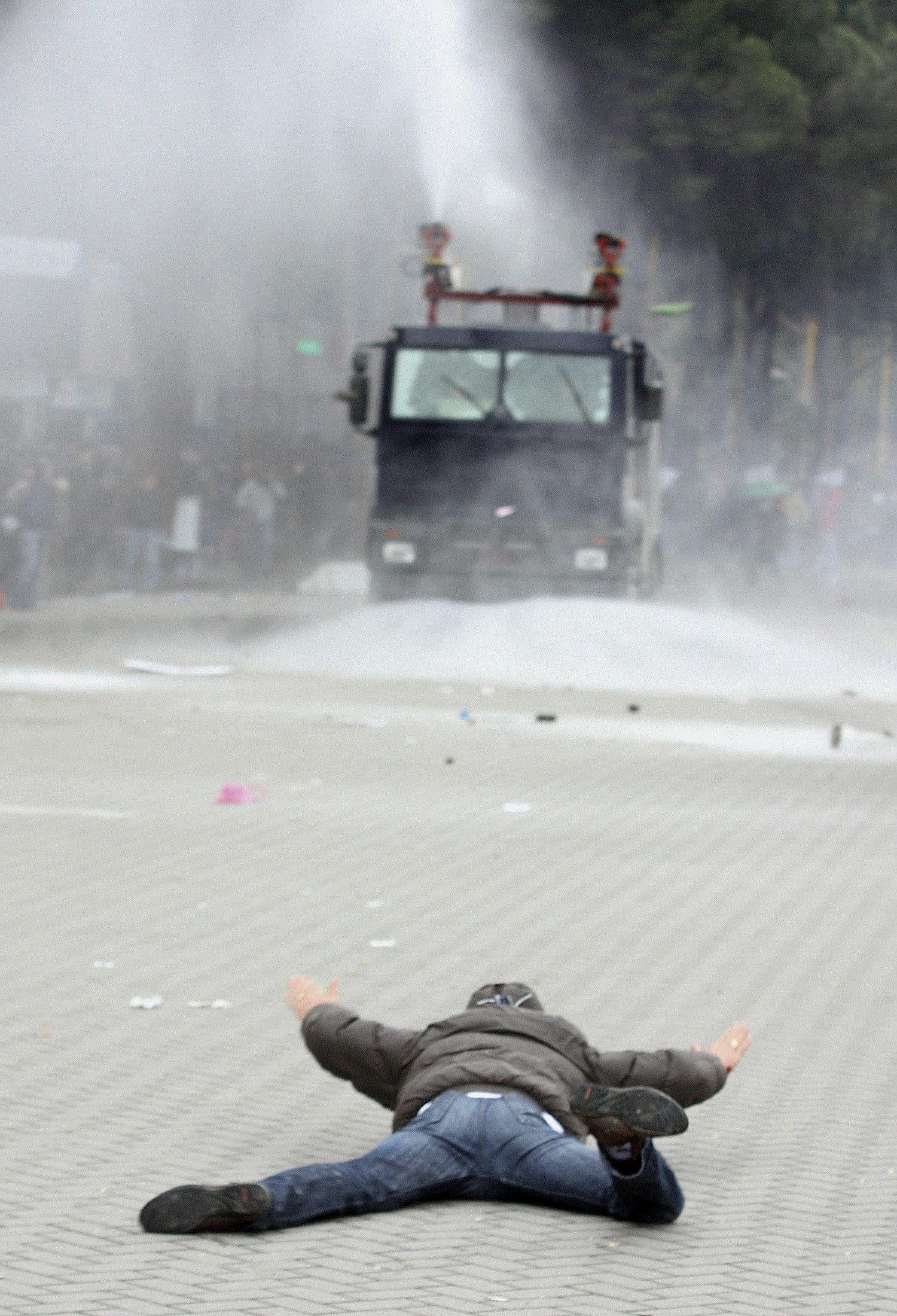 Διαδηλωτής στο έδαφος και στο βάθος οι αστυνομικές δυνάμεις - ΦΩΤΟ REUTERS