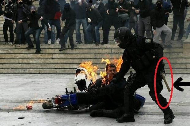 Συνάδελφος του αστυνομικού προσπαθεί να τον βοηθήσει. Εμφανές στη μέση του κι ένα δαυλί