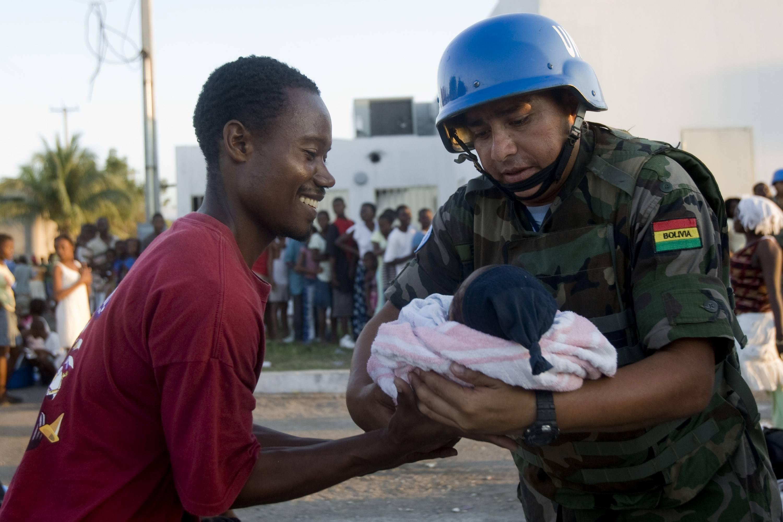 Ένας κυανόκρανος κρατάει ένα μωρό την ώρα που μοιράζεται φαγητό και νερό στους πληγέντες της Αϊτής ΦΩΤΟ REUTERS