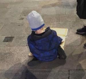 Ένα 5χρονο αγόρι τρώει το βραδινό του πάνω σε ένα χαρτόνι στον δρόμο