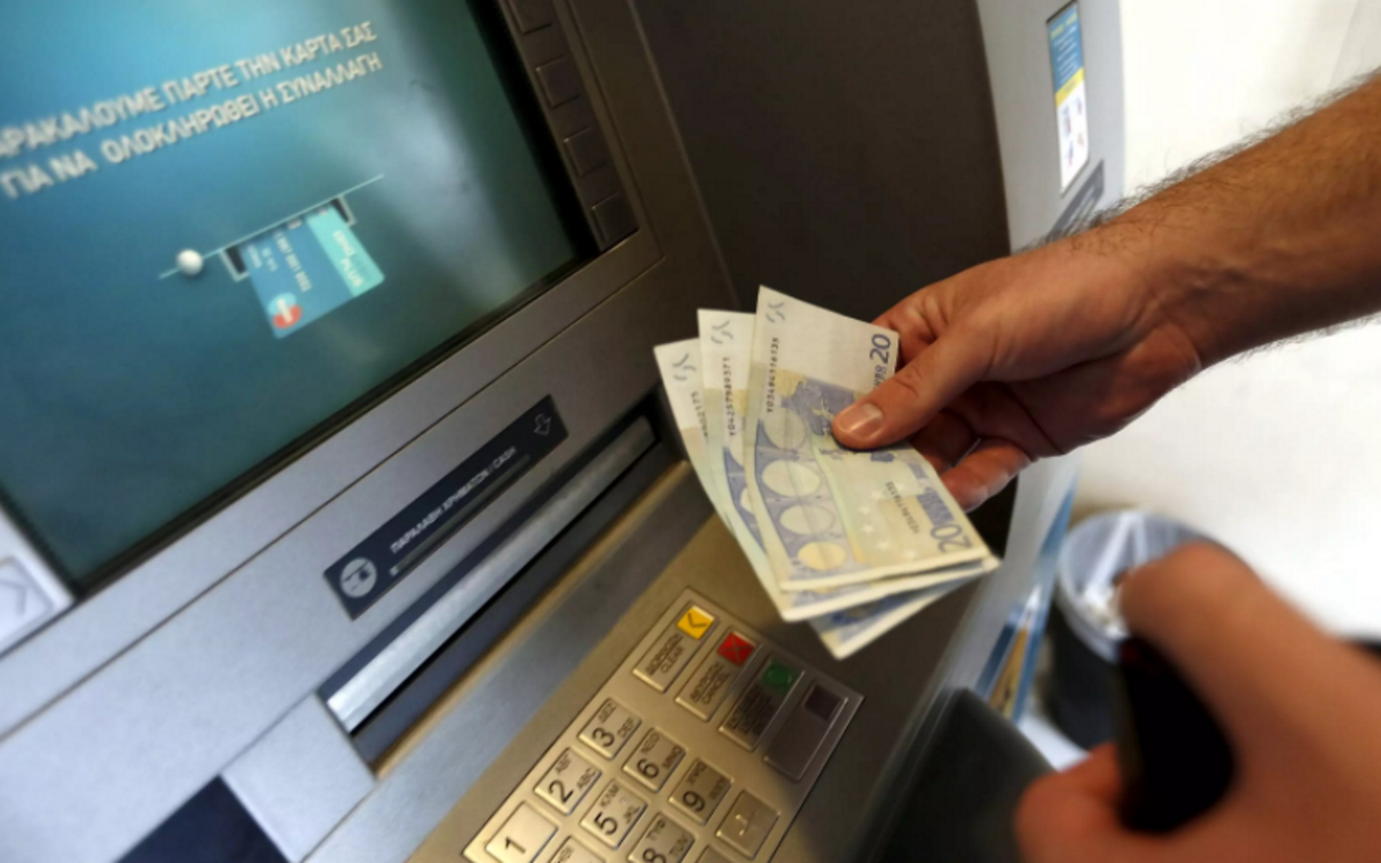 χαρτονομίσματα σε μηχάνημα ΑΤΜ