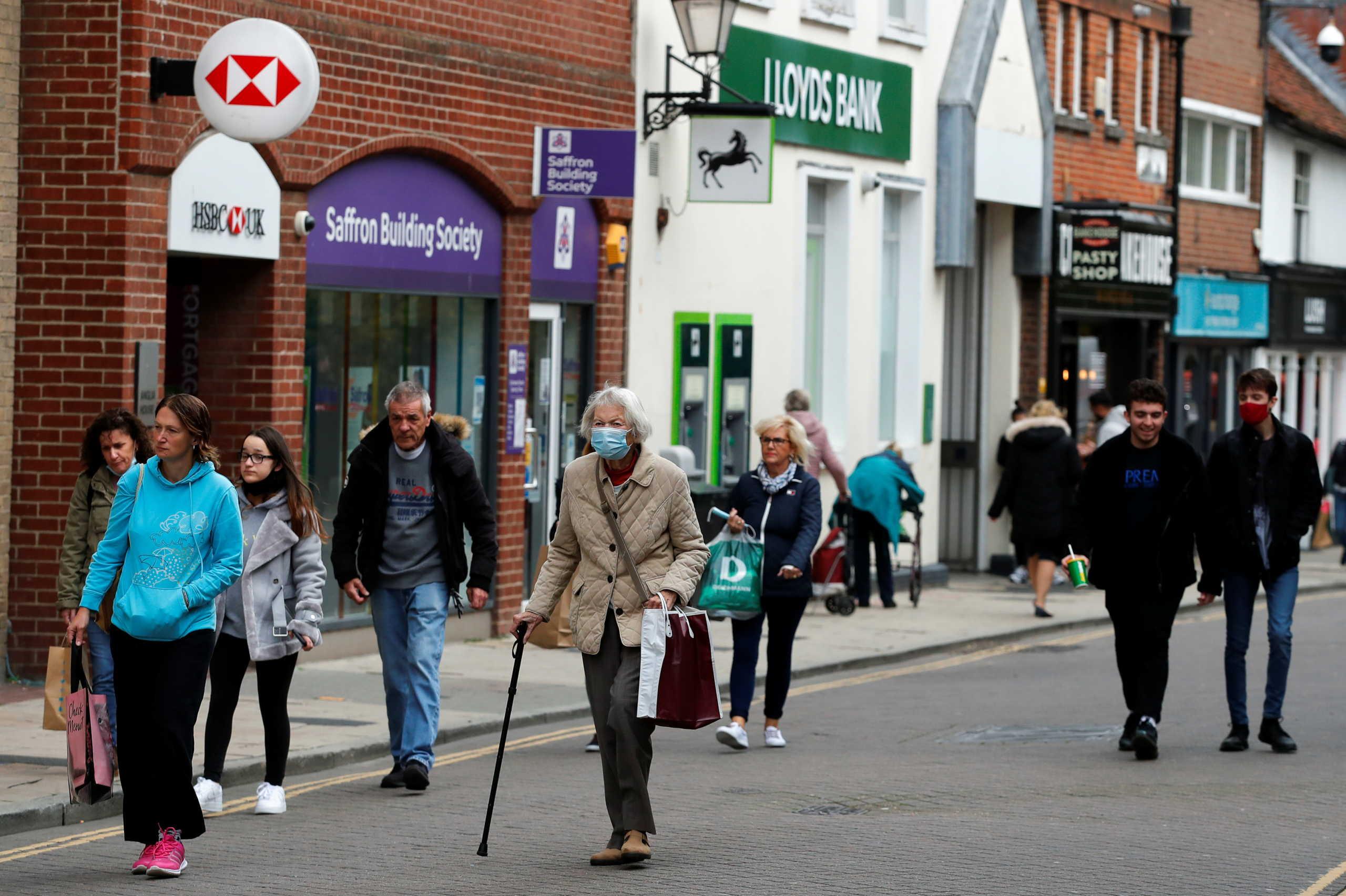 Γυναίκα με μάσκα για τον κορονοϊό περπατάει σε δρόμο στο Σάσεξ στη Μεγάλη Βρετανία
