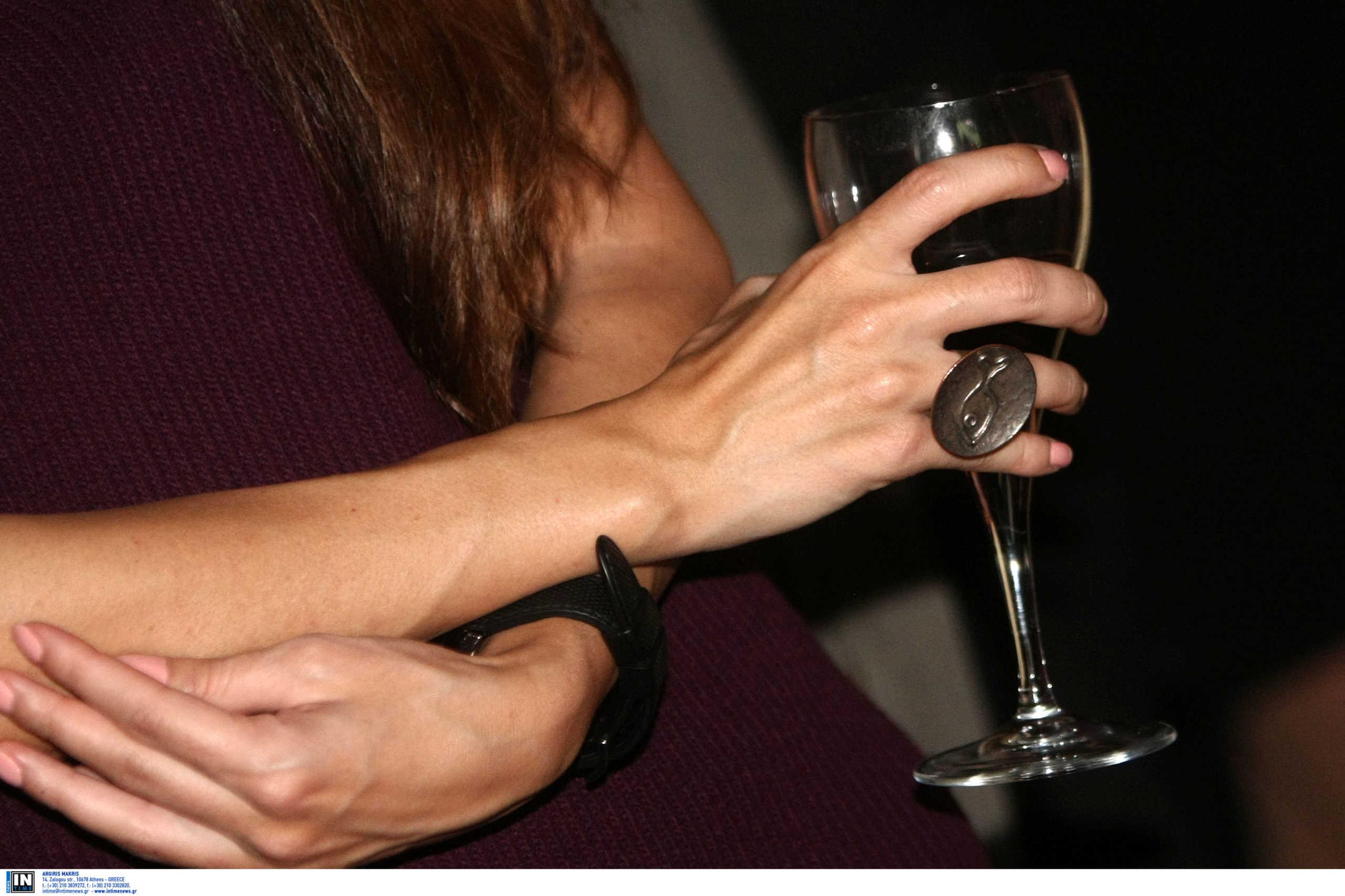 μία γυναίκα κρατάει ένα ποτήρι