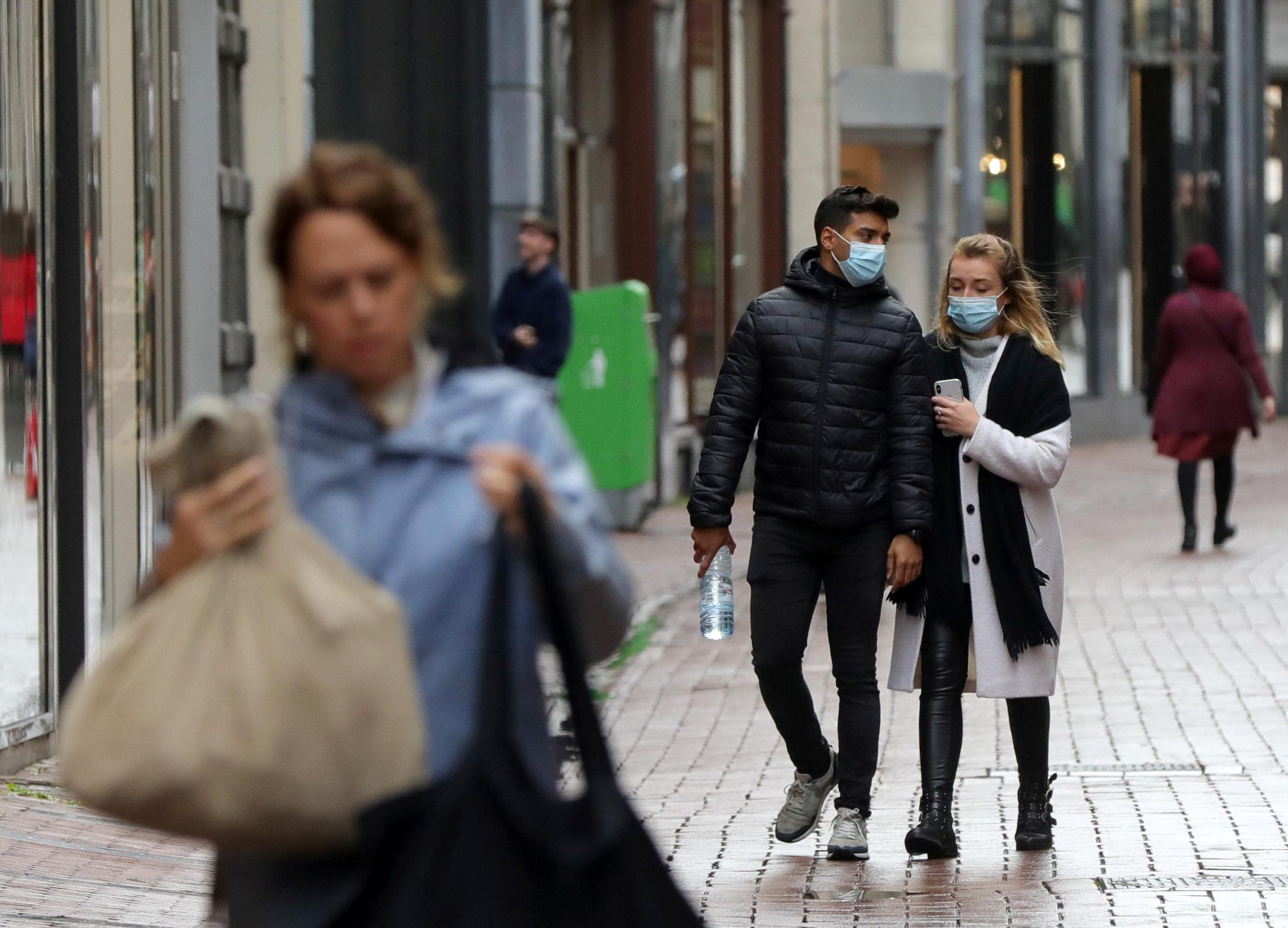 περαστικοί με μάσκα για κορονοϊό στο Άμστερνταμ