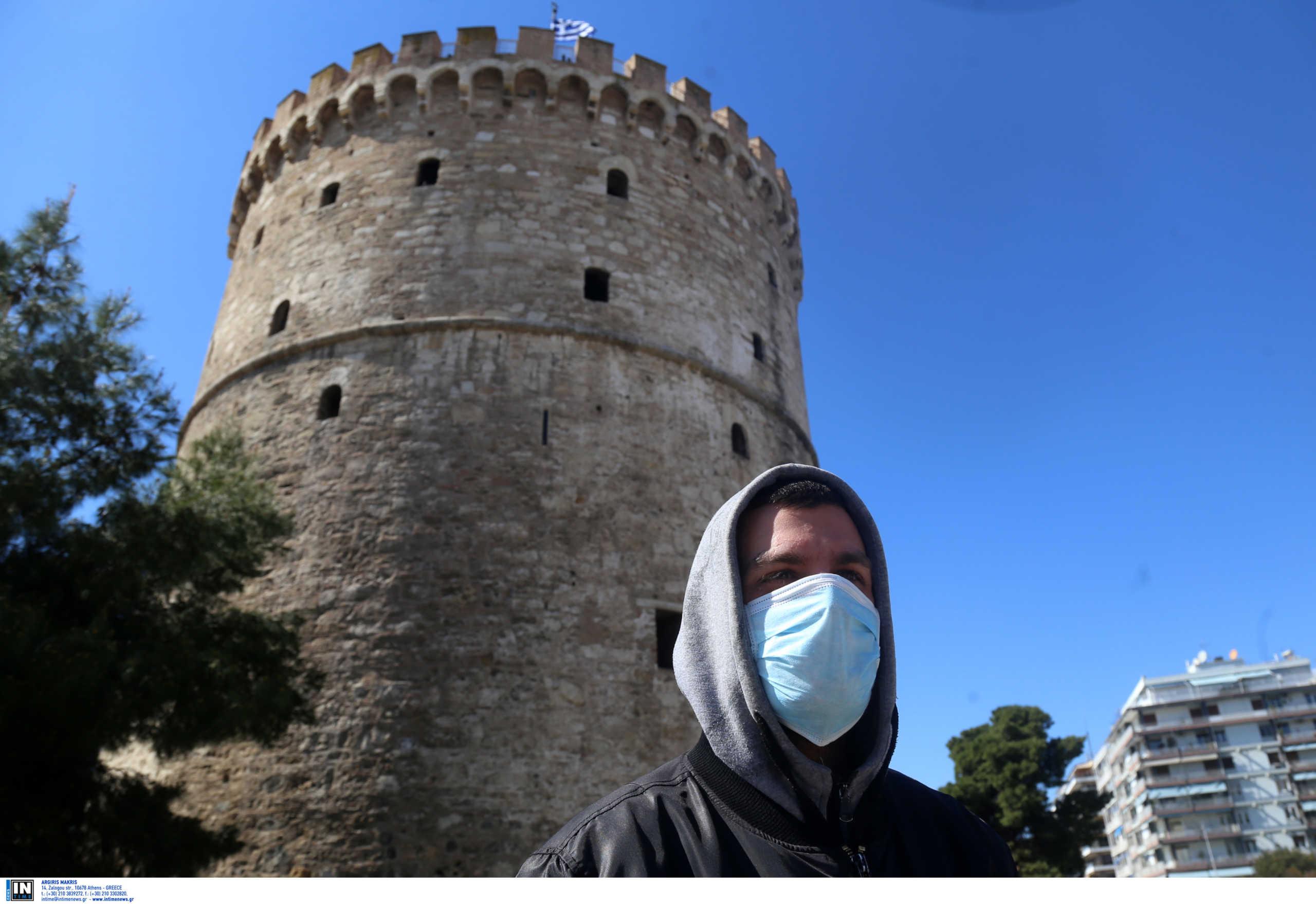 Νεαρός με μάσκα μπροστά από τον Λευκό Πύργο στη Θεσσαλονίκη