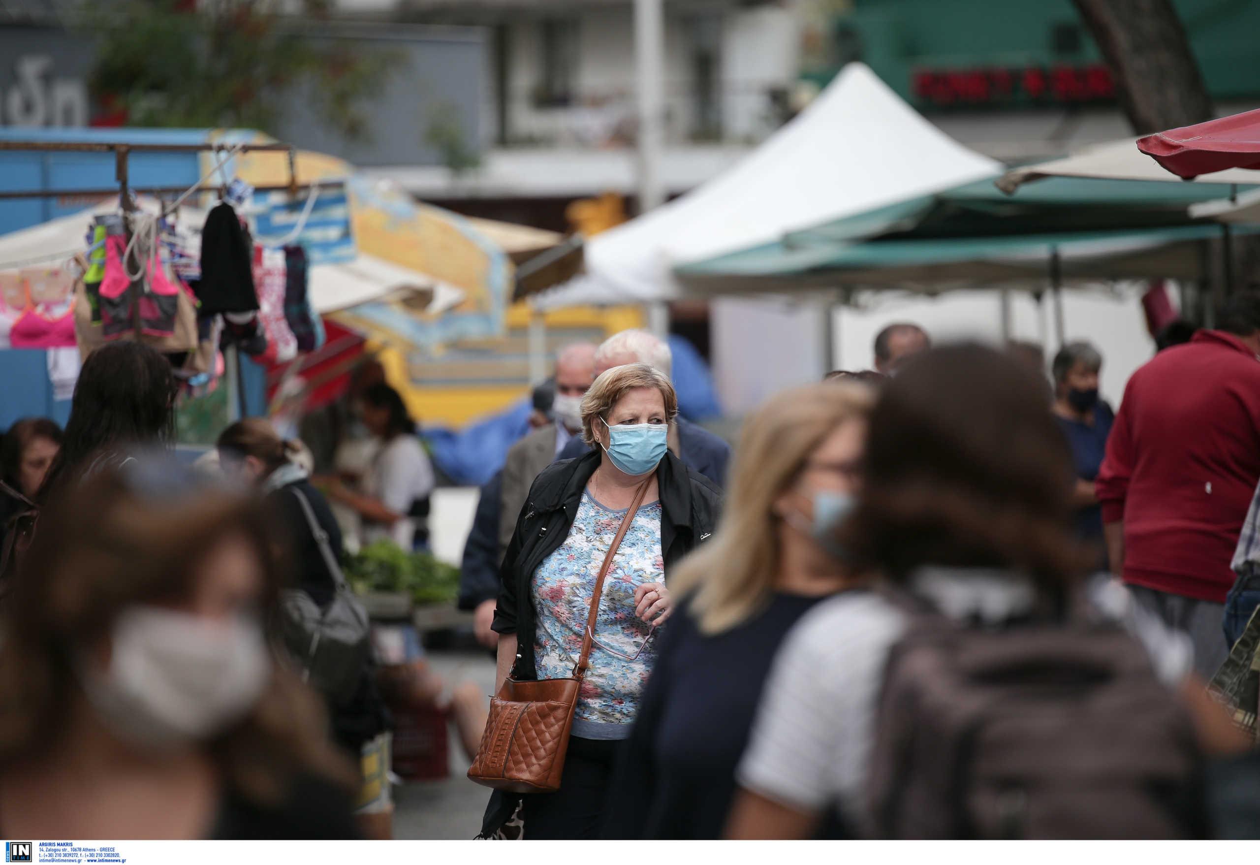 περαστικοί με μάσκα για τον κορονοϊό σε λαϊκή αγορά